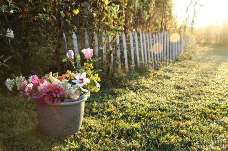 bucket of flowers at fence